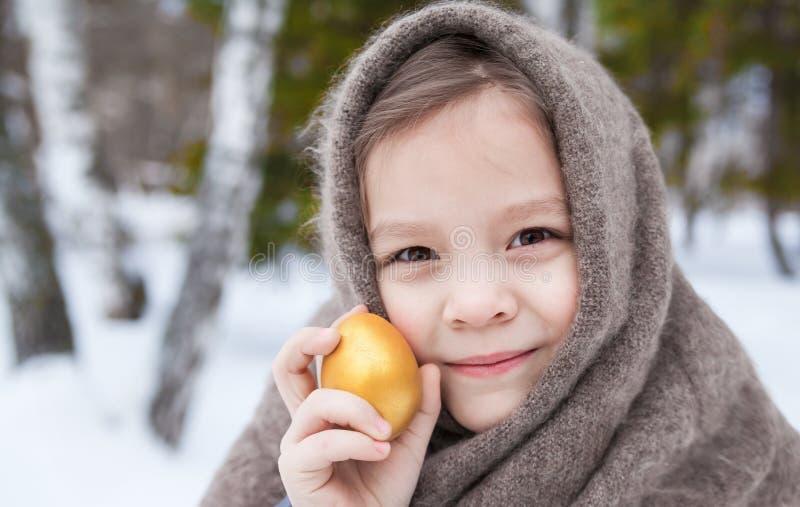一个小女孩的画象披肩和复活节彩蛋的 库存照片