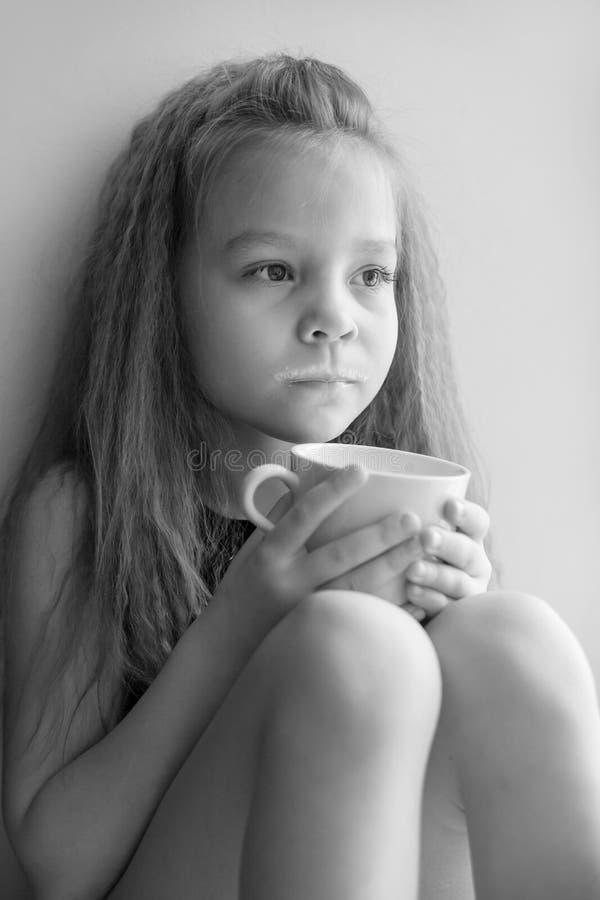 一个小女孩的画象有一杯的热的牛奶,黑白照片 免版税库存图片