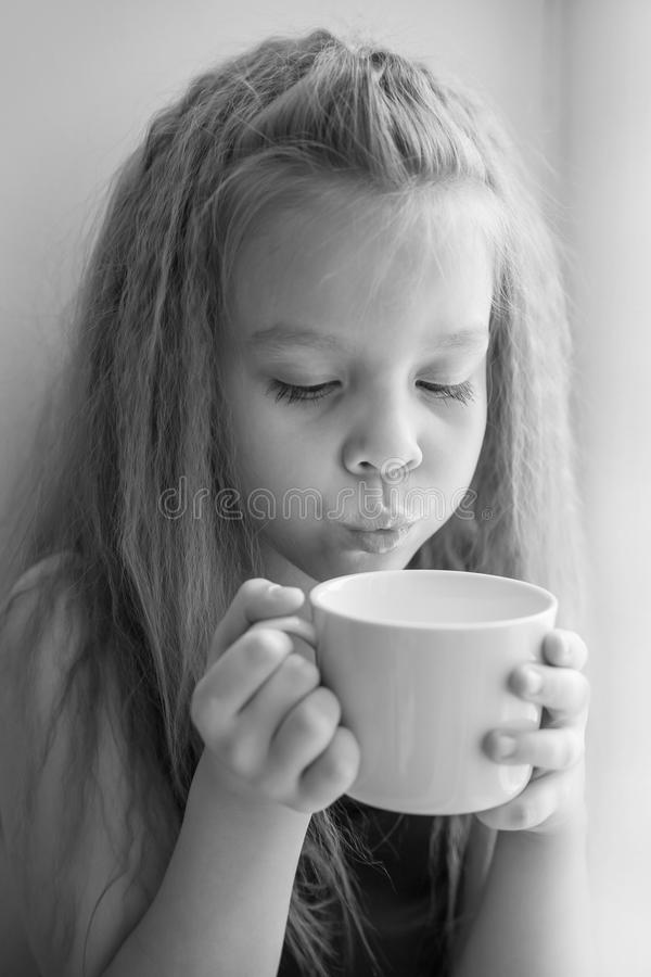 一个小女孩的画象有一杯的热的牛奶,黑白照片 免版税库存照片