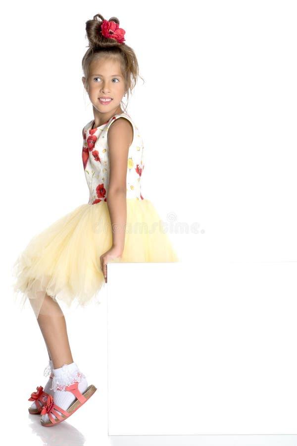 一个小女孩看从一副空的横幅的后面 库存照片
