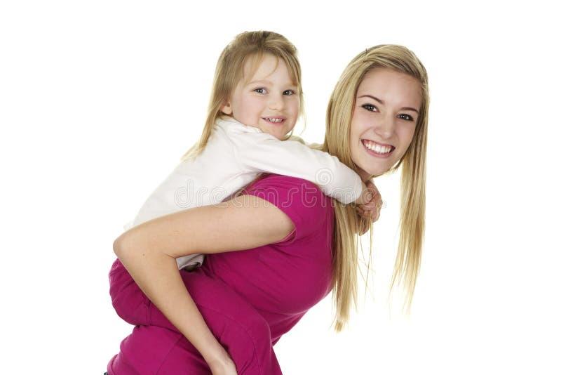 给一个小女孩肩扛乘驾的美丽的年轻保姆 免版税库存照片