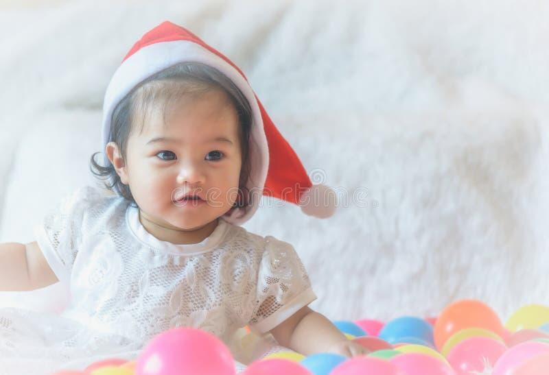 一个小女孩,圣诞老人帽子,充当她的床和colo 库存照片
