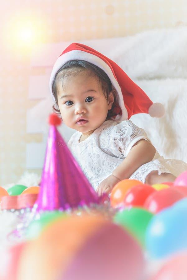 一个小女孩,圣诞老人帽子,充当她的床和colo 免版税库存照片