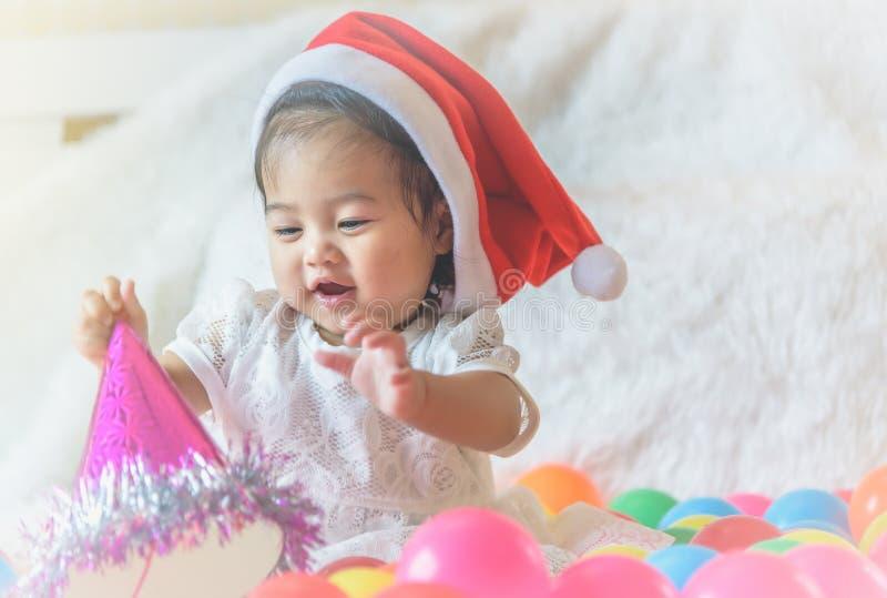 一个小女孩,圣诞老人帽子,充当她的床和colo 免版税图库摄影