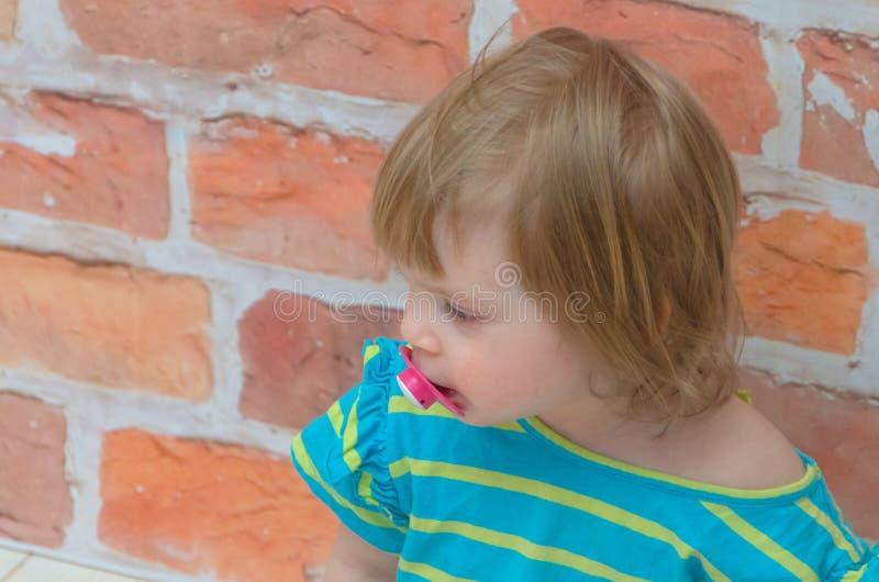 一个小女孩,有一名安慰者的一个孩子在砖w背景  免版税库存图片