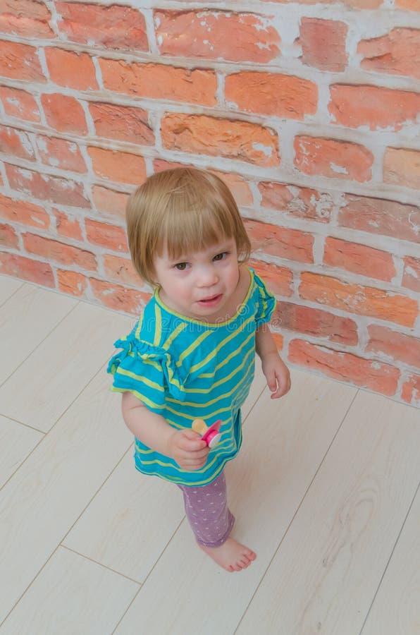 一个小女孩,有安慰者的一个孩子 库存照片