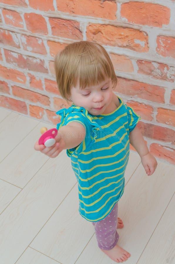 一个小女孩,有安慰者的一个孩子 免版税库存图片