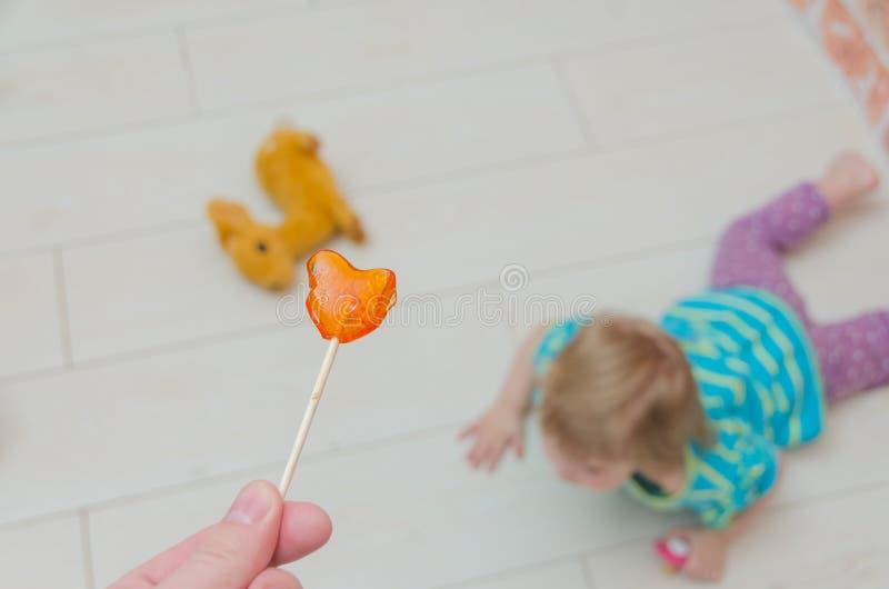 一个小女孩,有Lollipo的一个孩子 免版税库存照片