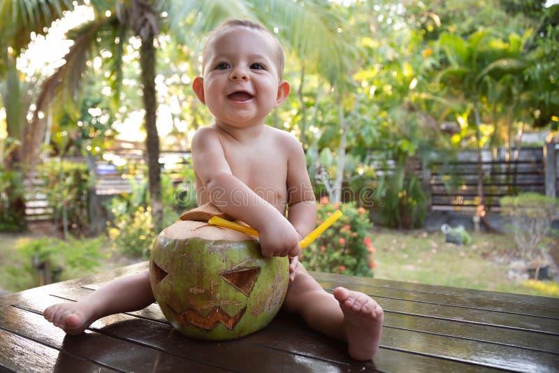 一个小婴儿从绿色椰子里取出一根稻草,这种椰子是万圣节标志的形状 免版税库存照片