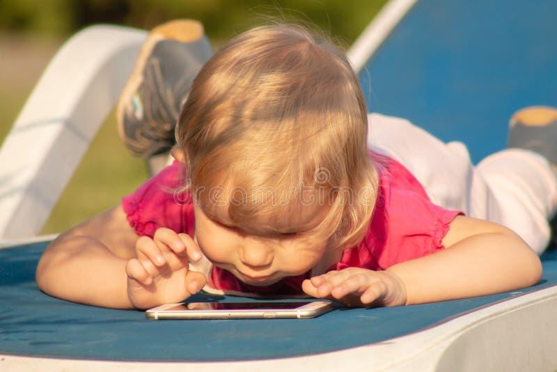 一个小孩在智能手机上热情地玩 免版税库存图片