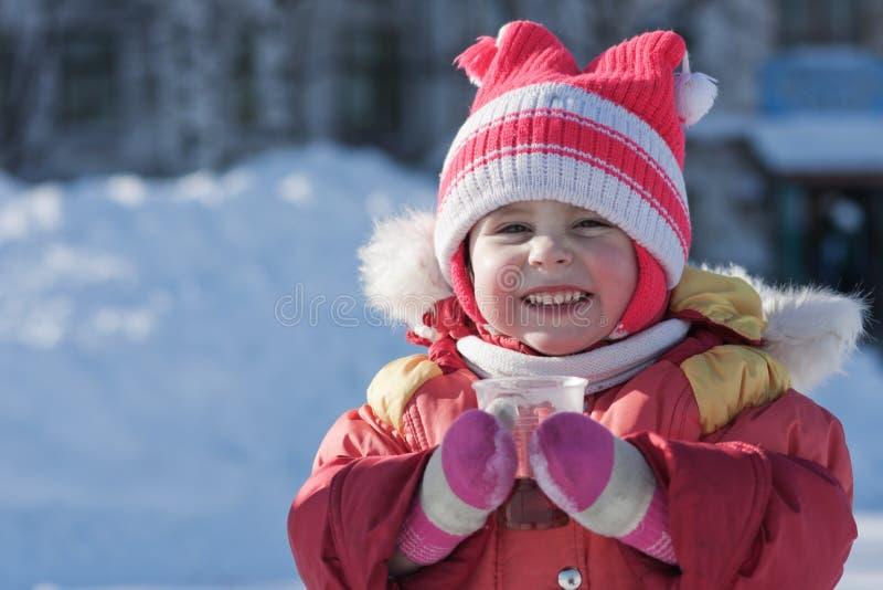 一个小孩子在冬天喝着一份热的饮料 免版税库存照片