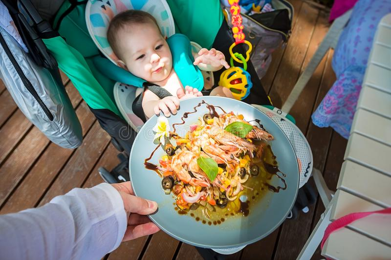 一个小孩子在8个月要吃成人食物并且拉扯虾和菜板材给他 坐在婴儿推车的婴孩 免版税图库摄影