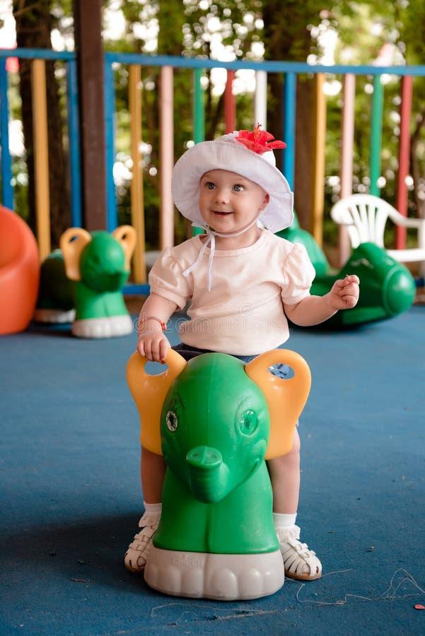一个小孩子坐一个绿色倾斜在操场并且微笑 免版税库存图片