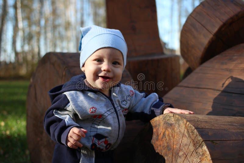 一个小孩子紧贴对一个微笑的夏天的木日志在公园 免版税库存图片