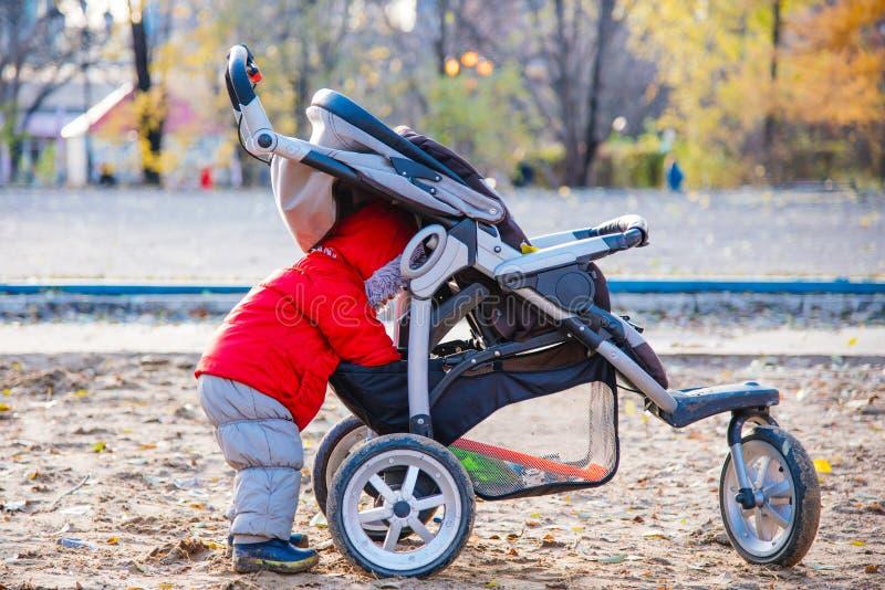 一个小孩子采取他的玩具在婴儿推车外面 库存图片