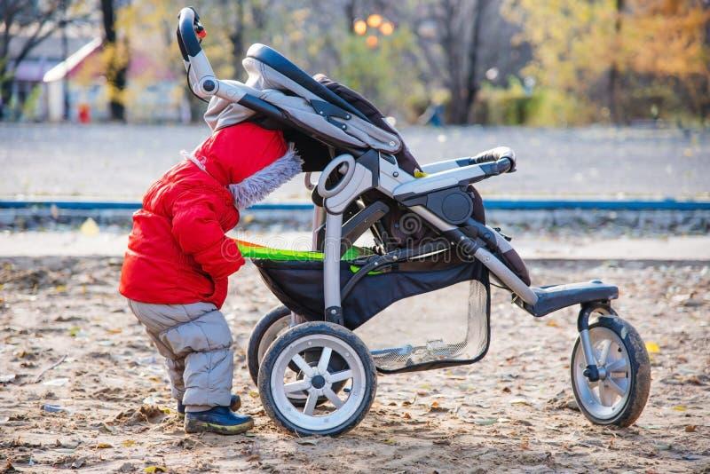 一个小孩子采取他的玩具在婴儿推车外面 免版税库存图片