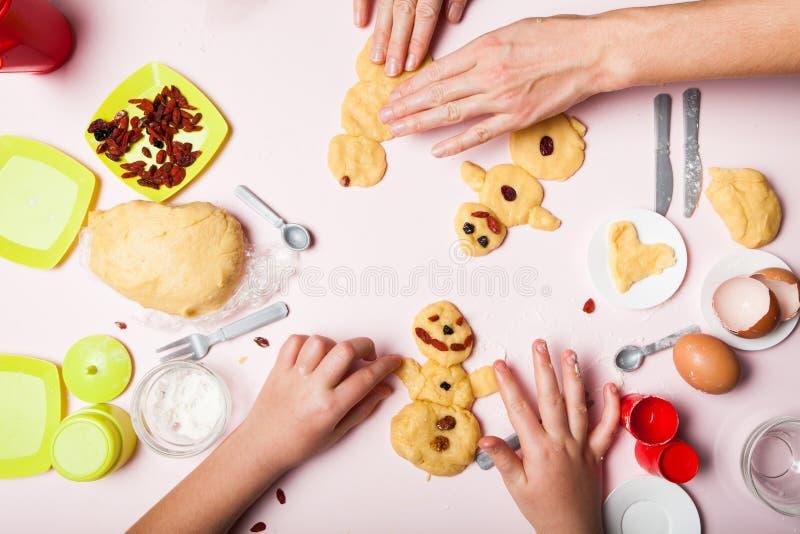 一个小少女女孩和母亲的手做酥皮点心曲奇饼 圣诞节烘烤 圣诞节姜饼以的形式 库存照片