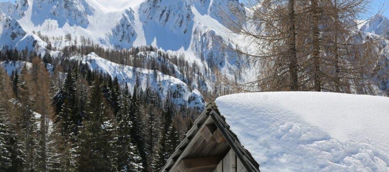 一个小屋的屋顶与雪的和山在背景中 库存照片