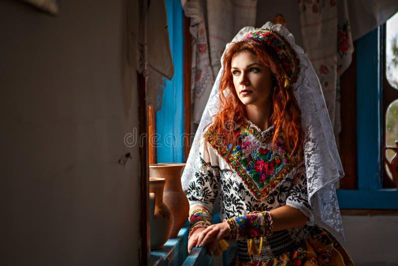 一个小屋的美丽的女孩在全国斯拉夫的服装 免版税库存图片
