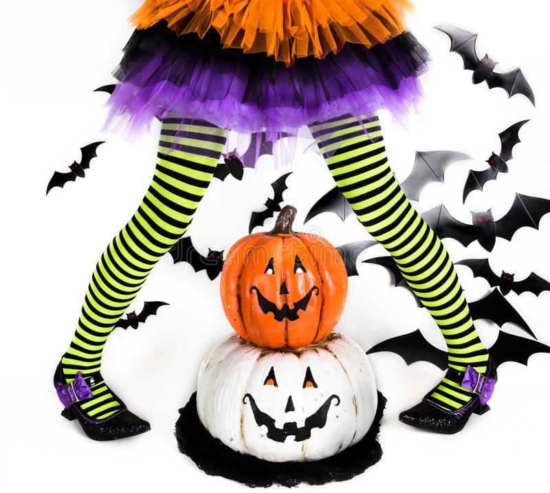 一个小巫婆女孩的镶边腿 万圣夜孩子、服装和装饰,万圣夜南瓜 库存照片