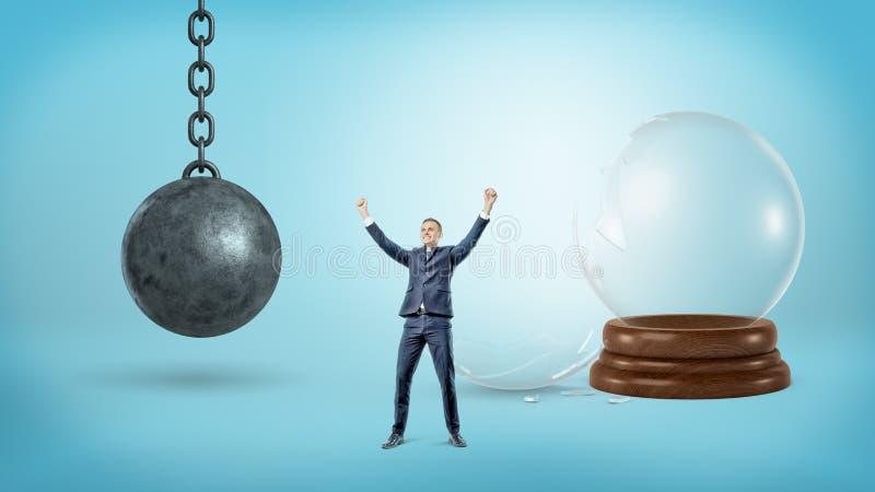 一个小战胜商人在击毁球的残破的玻璃球形和铁附近站立 免版税库存照片