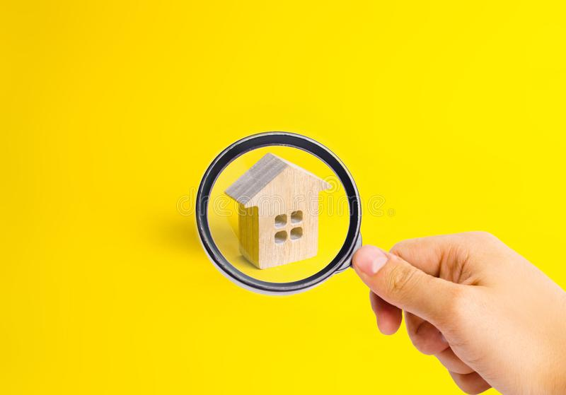一个小木房子在黄色背景站立 作为背景诱饵概念美元灰色吊异常分支 库存照片