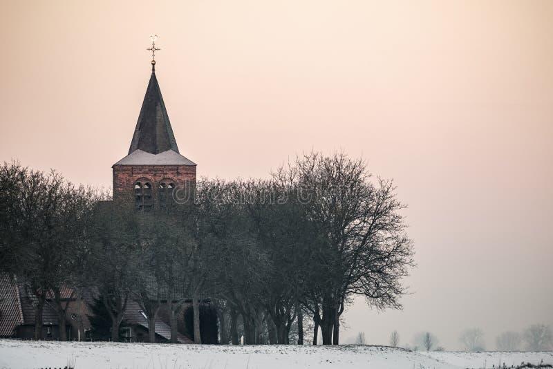 一个小村庄的教会和房子在堤堰后的 免版税库存照片