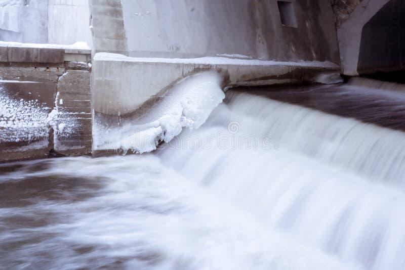 一个小水坝的溢洪道有冰冷的墙壁的 免版税库存图片