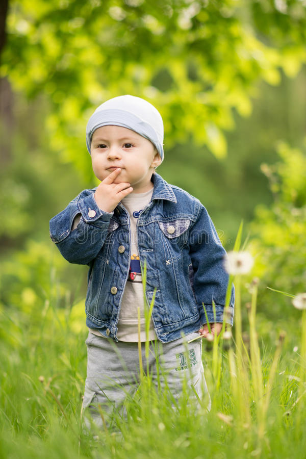 一个小沉思男孩在春天公园站立 免版税库存照片