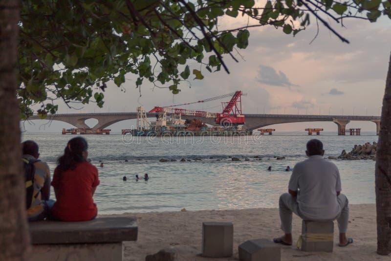 一个小海滩的人安装的和观看的沐浴者在男性,马尔代夫 免版税库存图片
