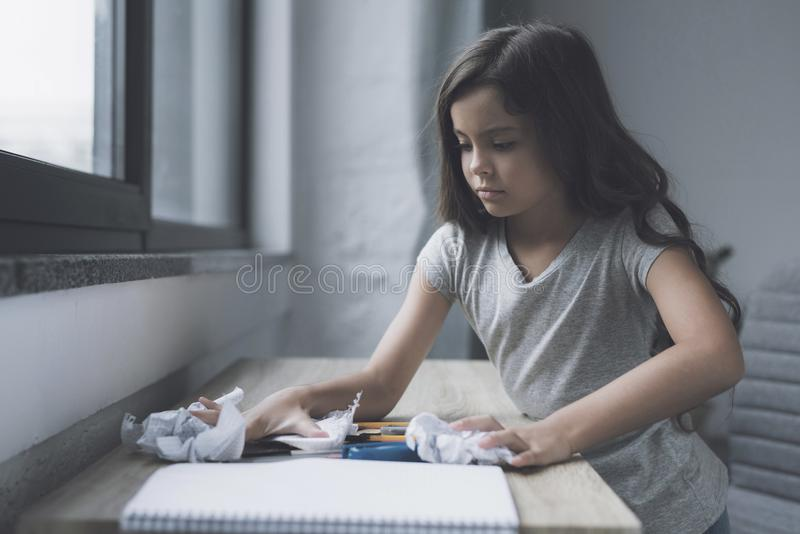 一个小深色头发的女孩在一张小桌上说谎在窗口附近站立的堆倾斜事 免版税库存照片