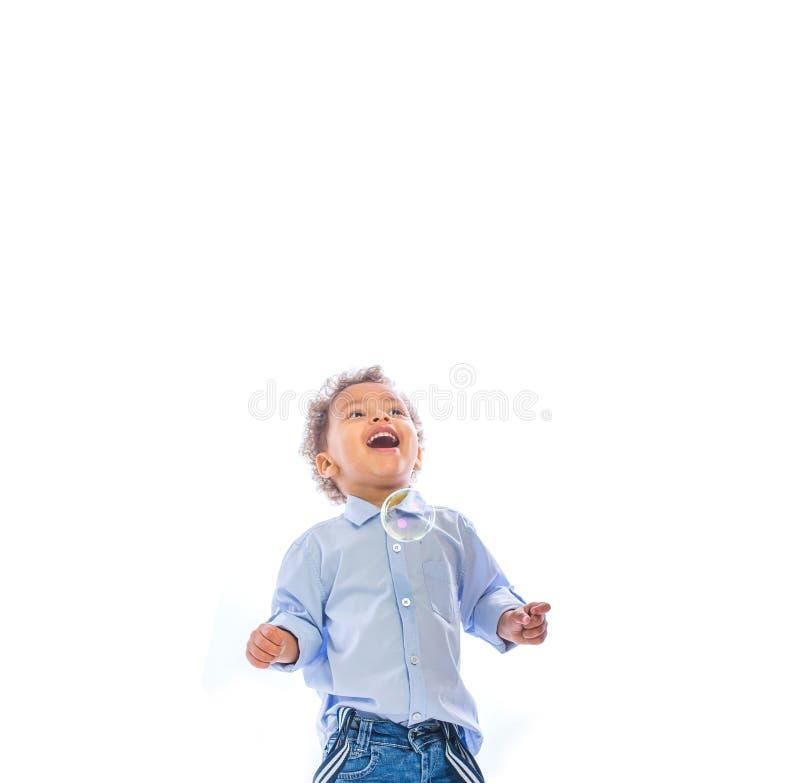 一个小深色皮肤的小孩的画象有查找的卷发的微笑看肥皂泡,被隔绝的背景 库存图片