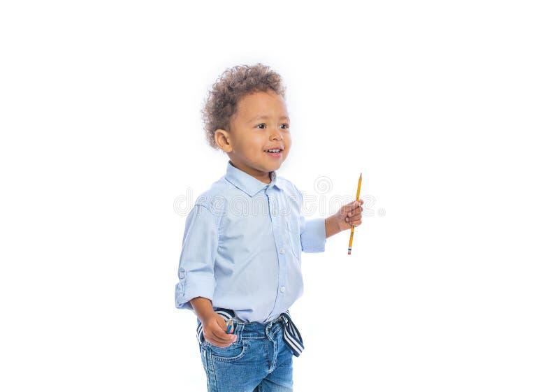 一个小深色皮肤的男孩的画象有卷发的在牛仔裤和一件淡色的衬衣在半轮站立 免版税库存图片