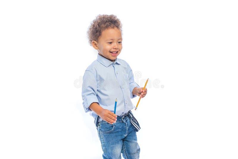 一个小深色皮肤的男孩的画象有卷发的在牛仔裤和一件淡色的衬衣在外形站立和 免版税库存照片
