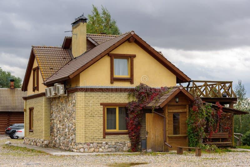 一个小现代房子由黄色砖和石头制成 库存照片