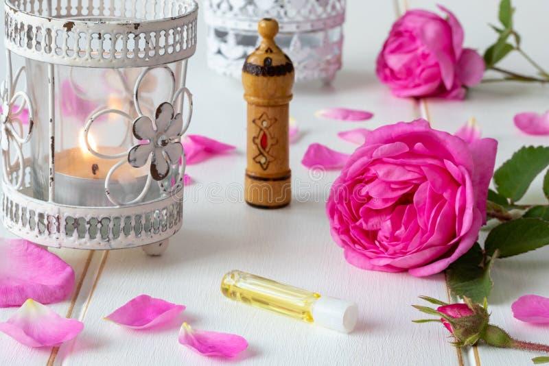 一个小瓶与新鲜的玫瑰色花的精油 免版税库存照片