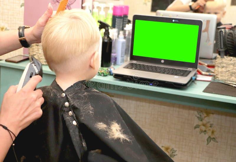 一个小男孩切开沙龙的一位美发师 孩子观看一部动画片 在一台膝上型计算机的绿色屏幕署名的 库存图片