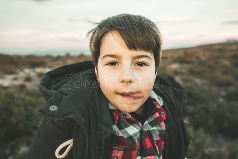 一个小男孩和微笑的画象有滑稽的表示的在乡下 愉快的子项 免版税库存照片