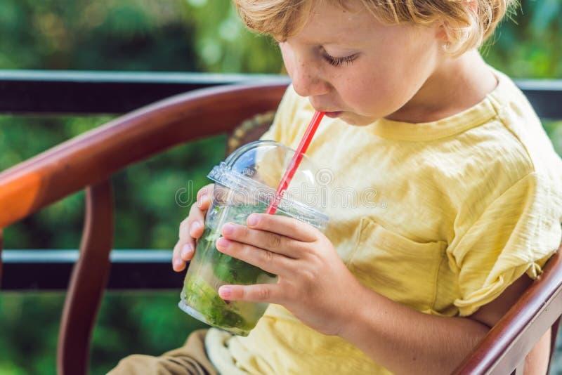 一个小男孩喝水用薄菏和石灰 喝更多水c 免版税图库摄影