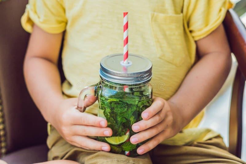 一个小男孩喝水用薄菏和石灰 喝更多水c 库存照片