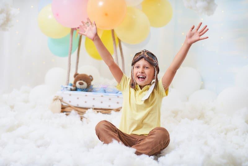 一个小男孩在云彩的一个气球篮子坐,假装旅行和飞行与创造性的概念的一个飞行员帽子 免版税库存照片