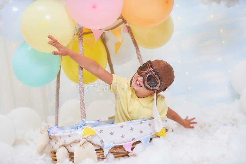 一个小男孩在云彩的一个气球篮子坐,假装旅行和飞行与创造性的概念的一个飞行员帽子 免版税图库摄影