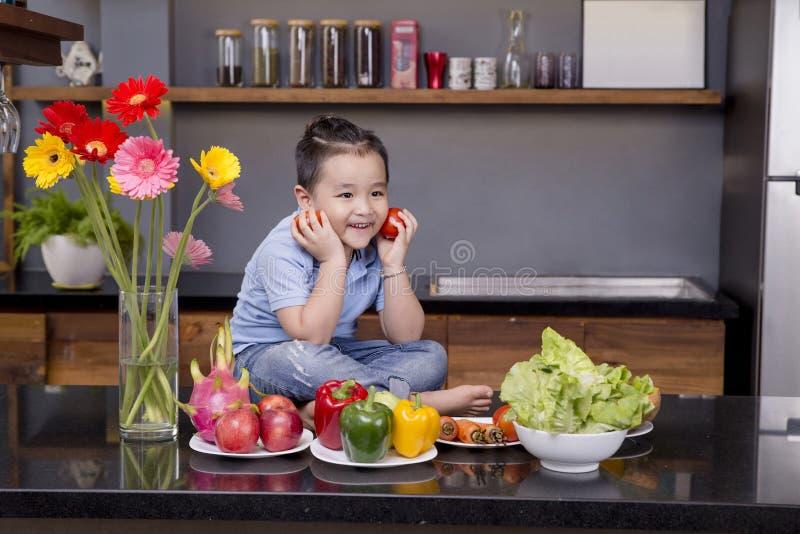 一个小男孩在厨房里用很多水果和蔬菜 库存图片