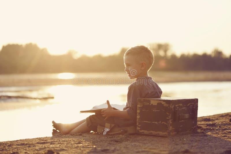 一个小男孩在含沙河岸使用在夏天在日落 免版税库存照片