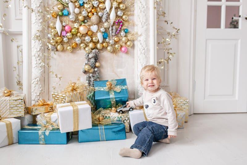 一个小男孩在很多礼物附近站立 新年好 圣诞节装饰了结构树 在明亮的生活的圣诞节早晨 库存图片