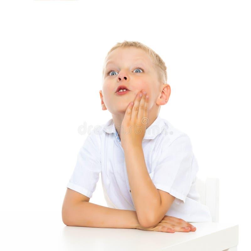 一个小男孩在桌上在学校做他的家庭作业 免版税图库摄影