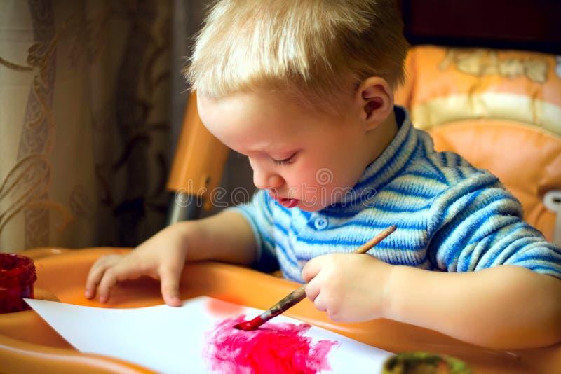 一个小男孩坐在孩子桌上,拿着刷子,油漆,油漆 免版税库存照片