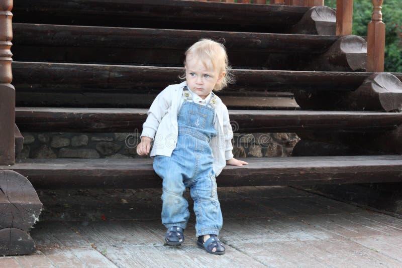 一个小男孩坐木台阶 免版税库存图片