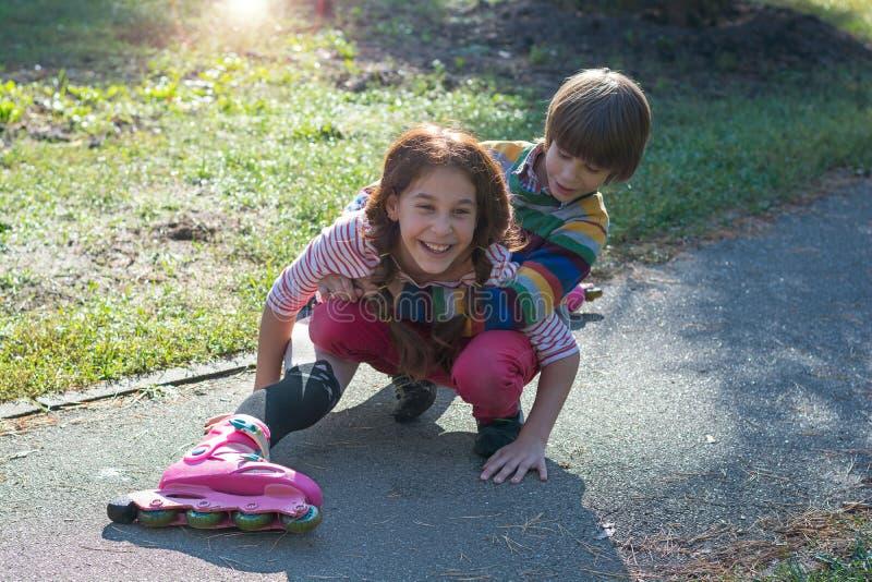 一个小男孩培养在溜冰鞋跌倒的他的姐妹 免版税库存照片