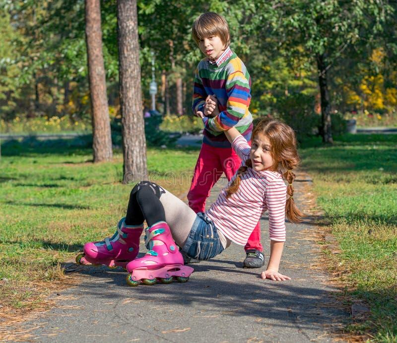 一个小男孩培养在溜冰鞋跌倒的他的姐妹 免版税库存图片